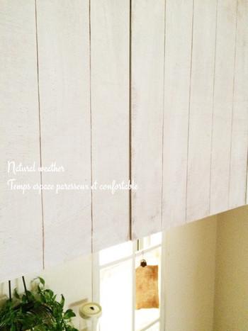 DIYは得意じゃないけれど、キッチンをイメージチェンジしたい!そんな方におすすめの吊り戸棚のリメイク。薄いベニヤ板に白いペンキをざっくり塗り、カッターで線を入れたら両面テープで吊り戸棚に貼るだけ。