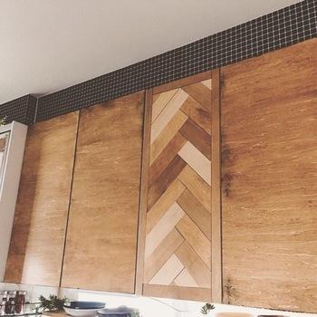 吊り戸棚の上の部分に、黒いモザイクタイルシールを貼ってカフェ風の雰囲気に。吊り戸棚の一部を木目調にするのも変化が生まれて面白いですね。