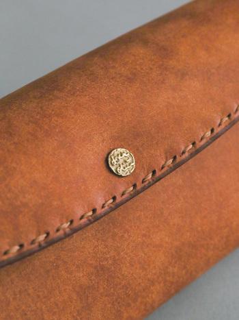 長財布のレザー特有の風合いは、栗の木、ミモザなどから採取される植物タンニンなめしの製法によるもの。ザラッとした表面が使い込んでいく程に艶がでてくるそうです。 大切に、ずっと愛用したくなりますね。