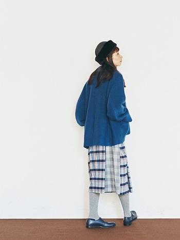スカートの柄からブルーを拾ってトップスに。タイツはスカートのトーンと同じ淡グレーを選び、着こなしにおしゃれな統一感を。