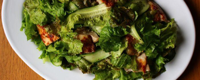 シンプルな生野菜にローストしたチキンを合わせたごちそうサラダです。チキンはドレッシングで下味をつけて焼いただけなのに本格的な風味になります。スーパーで手に入ったレタス類やキュウリなど生野菜とサックリと合わせるだけで出来上がり。