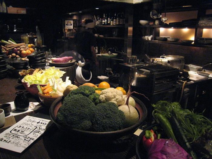 京都に来たら京野菜もしっかり味わいたいもの。そんな時におすすめなのが、河原町駅から徒歩1分という好立地にある【おにかい】です。カウンターには旬の京野菜が山盛り。スタッフさんが手際よく調理する様子を間近で見られます。