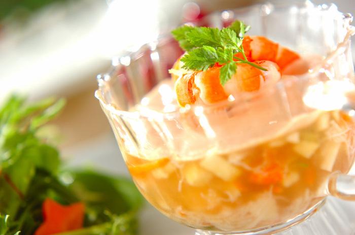 食事の最初に食べる前菜は、見た目も華やかだと嬉しいもの。こちらは、グラスと相性の良いゼリー寄せのレシピ。ニンジン、カブ、キュウリなどの野菜と、カニやリンゴが入っています。最後にエビを飾れば一気に華やかな一品に!ワイングラスなどの背の高いグラスを使うのもおすすめです。