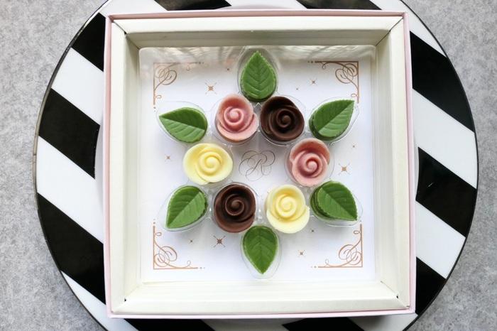 """箱を開けるとお花のリースが…♪こちらは、ミルク、ラズベリー、ホワイトの3種類のショコラローズと、抹茶のリーフでできたチョコレート。商品名は""""クロンヌ""""で、幸福や平和そして永遠のシンボルである花のリースを意味しているそうです。都内には他にも3店舗あるので、ぜひ立ち寄ってみてくださいね。"""
