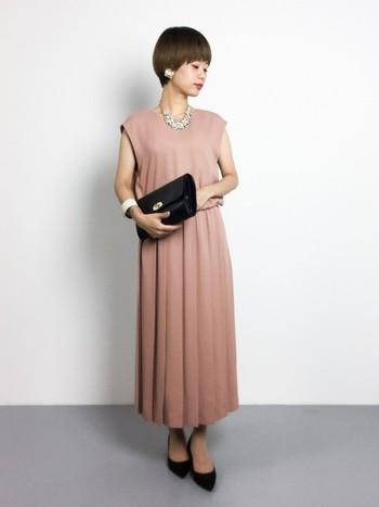 女性らしい優しいピンクベージュのドレスには、ボリューミーなネックレスやブレスレット、イヤリング・ピアスをあしらって、シンプルになりすぎないように。  アクセサリー以外の小物はブラックで統一するのがおしゃれポイント!