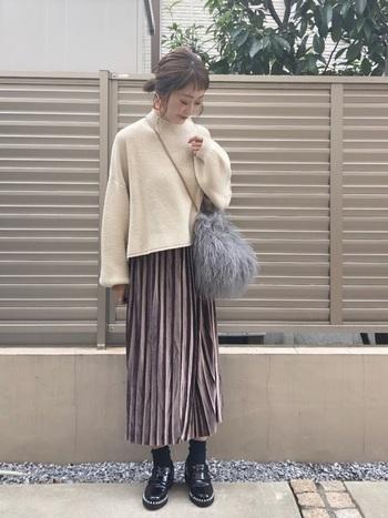 袖などのフォルムがぽわんとした白ニットは、今流行の「in」にはせずに、ベロアのプリーツスカートの上に出して。ニットのデザイン性を楽しめるコーデにしましょう。