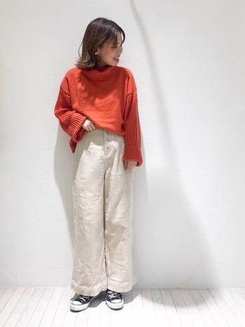 """オーバーサイズのニットを主役にするために、白いワイドパンツを潔く合わせました。パンツスタイルなのに女性らしく見えるのは""""白×オレンジ""""がハートウォーミングかつ爽やかな印象の配色だから。"""