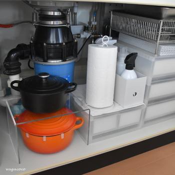 排水管の周りの凸凹した空間は、活かしくいですよね。 そんなときは、アクリル仕切棚を設置するのがおすすめ。 あまり高さのない鍋などを収納するのに重宝します。  置き場に困るキッチンペーパーは、自立式のペーパーホルダースタンドを利用すれば、手軽に縦置きできます。
