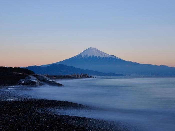 駿河湾の向こう側に富士山がそびえ立つ絵葉書のような絶景。これは、三保の松原から撮影されたものです。冬は雲が晴れていることが多く雪が積もる富士がくっきり見えます。「神の道」と呼ばれる松並木の参道を通ると、そこには天女の羽衣伝説で知られる羽衣の松が。
