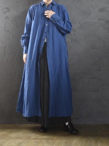ブルーのシャツワンピースに、黒のワイドパンツを合わせたコーディネートです。シューズも黒で合わせて、まとまり感のある着こなしに。ボタンは上の方だけ留めて、ワイドパンツのボリューム感をアピールしているのがポイントです。