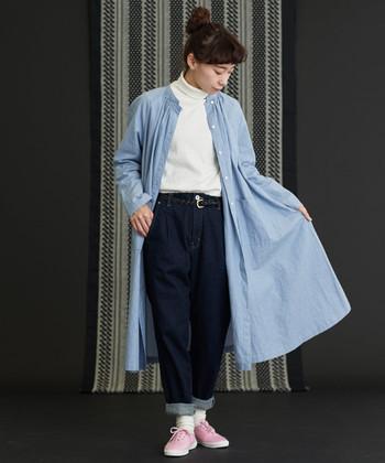 白のタートルネックに、スタンドカラーのシャツワンピースを羽織ったスタイリングです。ちょっぴりワイドなデニムパンツにタートルネックをゆるっとタックインして、ナチュラルなコーディネートに。
