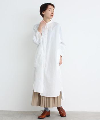 丈が長い白のシャツワンピースに、ベージュのプリーツスカートをレイヤードした着こなしです。茶色のマニッシュシューズで、一層ナチュラルな雰囲気に。