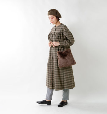 グレンチェック柄のシャツワンピースに、グレーのパンツを合わせたスタイリング。ベレー帽や茶色のファーバッグで、季節感とトレンド感をしっかりアピールしています。