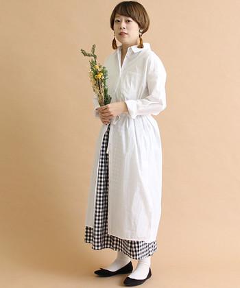 白のシャツワンピースに、チェック柄のスカートを重ねたコーディネートです。ウエストでリボンを結び、そこから下のボタンを開けることで、エプロンワンピースのように着こなして♪