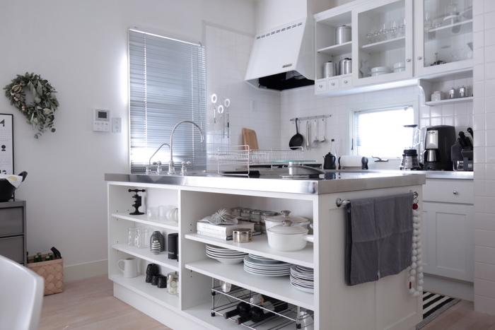 こちらも白いインテリアで統一された、上品で爽やかな雰囲気のキッチンです。おしゃれなアイランドキッチンには、オープンシェルフが付いていて収納力も抜群。奥行きもあるので器や調理道具をたくさん収納できますが、オープンタイプは雑多な印象になりがちなのが悩みだったそうです。