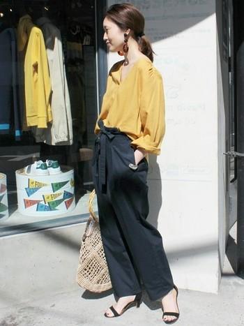 ワイドなネイビーパンツには、ヒール靴を合わせて女性らしさをアップさせてみてはいかがでしょう?ヒール付きサンダルとマスタードイエローのゆったりブラウスがフェミニンな雰囲気です。
