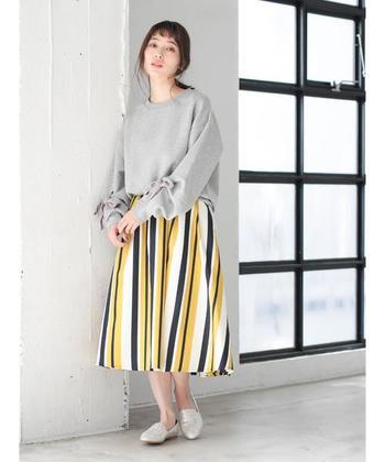 こちらはランダムな印象を与える、爽やかなストライプ柄。ふんわりとしたスカートのシルエットが、柔らかな女性らしさを生み出します。