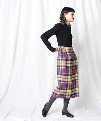 艶やかなカラーリングのチェックのタイトスカートにはシンプルに黒いニットをinして、スカートの美しさを引き立ててあげましょう。