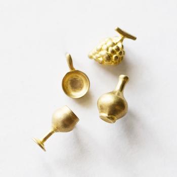 真鍮でできた小さなブローチのモチーフは、絵本の世界から飛び出してきたような可愛らしいミニチュア。デキャンタに葡萄、グラスなどなど10種類。組み合わせた胸元で、ストーリーを感じさせてみるのも◎