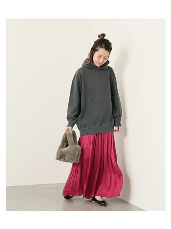 派手めカラーのスカートには、暗めグレーのフーディーを。派手になりすぎない、バランスのよいコーディネートの完成します。