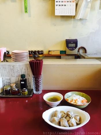 カウンター席の赤いテーブルが可愛い!初めて訪れたら、まずは「水餃子」から。コロンと丸っこい餃子は「白菜と生姜」や「大根と搾菜」など種類が豊富です。