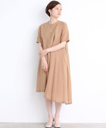 プレーンな印象を持ちながらも、アシンメトリーにデザインされた裾が自分らしい個性を引き出してくれる、ベージュのドレス。
