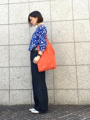 鮮やかなブルーのシャツにネイビーパンツを合わせた同系色でまとめたコーディネート。オレンジのバッグを差し色に加え、レトロポップな印象を作りながらも品良くまとめています。