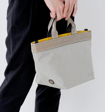 ナイロン素材の小ぶりなトートバッグは、軽くて扱いやすいのが魅力のアイテムです。シンプルデザインにラメテープが施されているので、さりげない大人デザインに仕上がっています。