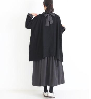 シンプルな黒のワンピースは、首の後ろ側に施されたリボンがワンポイント。黒のカーディガンを羽織ってリボンを外側に出すコーディネートで、さりげないフェミニンさを演出しています。黒コーデなら、大きめのリボンも甘くなりすぎませんね。