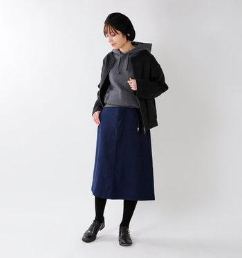 フードのかわいいグレーのパーカーには、ネイビースカートと黒タイツがぴったり! 着回ししやすいダークトーンのアイテムでまとめつつ、重ね着をしても重たく見えない冬コーデです。
