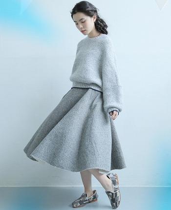 ふわりと広がるシルエットが女性らしい、グレーのサーキュラースカートに、グレーのニットを合わせたワントーンコーデです。グレー一色で控えめな着こなしにならないよう、デザイン性のあるシューズを合わせているのがポイント。