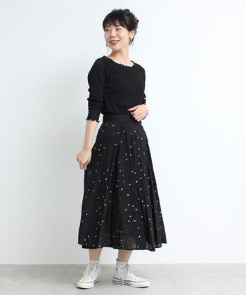 シンプルな黒のサーキュラースカートに、刺しゅうを施したデザインが素敵。黒トップスと合わせたワントーンコーデに、白のスニーカーがグッと映える着こなしです。