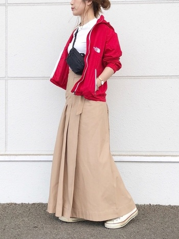 真っ赤なシェルが主役のこちらのコーデは、街でも目をひきそう。インナーのTシャツをロングスカートにインして、メリハリあるシルエットに仕上げて。