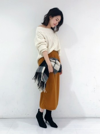 ベルベッド素材のコクーンスカートは、白のオフショルニットを合わせてフェミニンな着こなしに。チェック柄の大判ストールをサッと羽織れば、春までOKのこなれコーデが楽しめます。