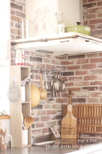 使い込んだ風合いのレンガ柄の壁紙を使って、温かみのある外国風のキッチンに。吊り下げて収納しているツールたちも絵になります。