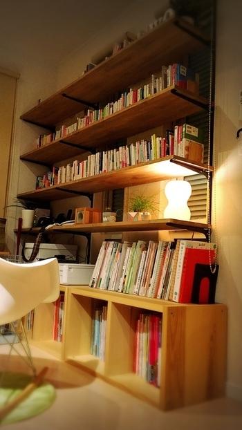 壁一面にDIYで設置されたこちらの本棚は、柔らかなライトの光に照らされ、ほっとくつろげる雰囲気ですね。  市販の「下地センサー」等で壁の下地のある場所を探して棚柱(ロイヤル製チャンネルサポート)を取り付けたら、棚受(ブラケット)を設置。棚板を置けば完成とのこと。自分好みの壁面本棚が欲しい方はチェレンジしてみては?