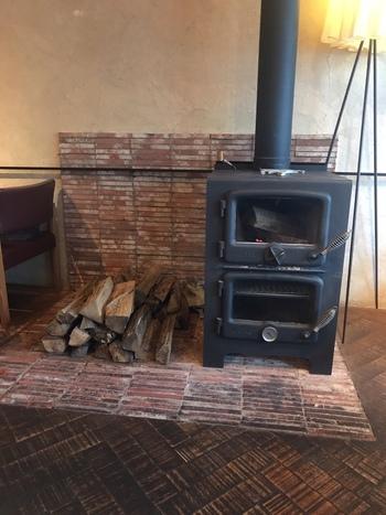 「札幌本店」には、軒先そして店内に高く薪(まき)が詰まれ…冬は、店内にある薪ストーブがその空間を優しく包み込むようにあたためてくれます。