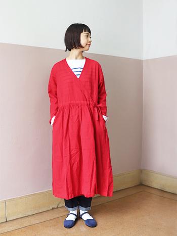 ウール×リネンのカシュクールワンピースは、レイヤードで着るのがおすすめ。紐をきゅっと絞れば可愛らしく、開けて羽織るように着ればクールな着こなしに。インナーの色選び次第で、赤ワンピの表情もどんどん変わりますよ。