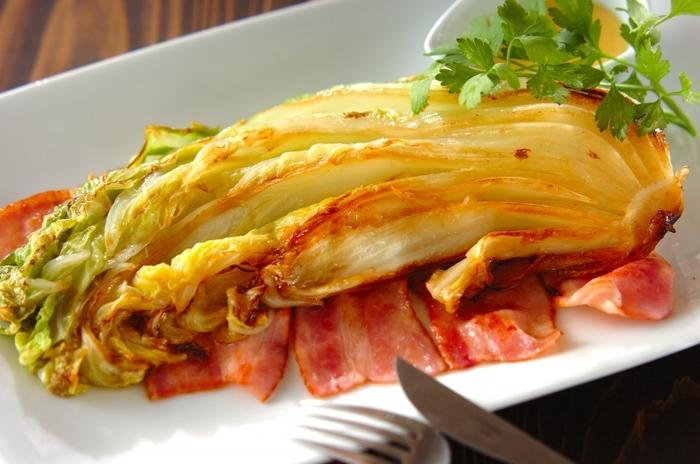 白菜の長さを生かしたダイナミックな焼き白菜。バラバラにならないよう芯は付けたまま焼きます。ベーコンのコクと卵黄ソースのうまみで、シンプルながらもくせになる味。白菜の甘みが存分に味わえます。