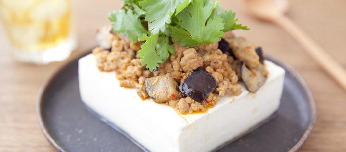 絹ごし豆腐といえば、冷奴(ひややっこ)。しょうがやみょうがなど薬味をのせていただくのもおいしいですが、アレンジすれば立派なメインのおかずに。 こちらは、豆板醤やしょうゆなどで味付けた挽き肉となすをのせたボリューミーな一品です。