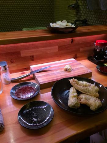 それでは、「ホルモン天ぷら」を注文しましょう。  そこで出てくるのが、なんと、まな板と包丁!そう、こちらのお店は、揚げたてのホルモン天ぷらを、セルフカットでいただくスタイルなんです。  そのままで噛み切れない訳ではないですが、モッチリしているので、自分にあった一口サイズに切っていただけるのはいいですね。これぞ「ホルモン天ぷら」の醍醐味♪