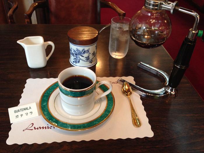メニューは「ルミエールブレンド」をはじめ、1000円以上のコーヒーまで様々。 ポットから注ぐコーヒーは薫り高く、最高学府の店名にも納得の深い味わいを楽しめます。テーブルセッティングやカップの装飾にもこだわりを感じられますよ。