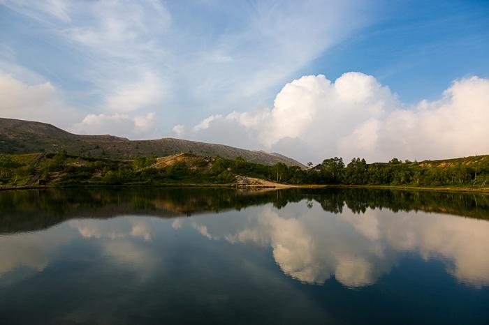 湯釜の駐車場の道路を挟んで反対側にある、緑の美しい「弓池」。周囲は湿地帯で、ワタスゲやモウセンゴケなど湿生植物が見られます。湖に沿った遊歩道は、1周20分ほどで森林浴が楽しめます。風が穏やかな日は湖面に映る雲や緑がとてもキレイ。  ※草津白根山エリアは、火山活動の状況により立ち入りが規制される場合があります。また、11月中旬~4月下旬頃は通行止めになるので、詳細は道路交通情報をご確認ください。