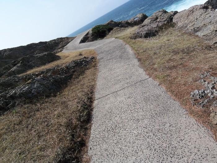 美しい夕日が見える場所としても有名な日御碕(ひのみさき)。  ドラマティックな神話が残っている場所ではありませんが、日本海と夕日の景色はもちろん、断崖絶壁、奇岩など・・・自然美と大きなパワーを、思いっきり体感できる場所。  お目当ての日御碕灯台までは、このような狭い遊歩道をすこし歩きますが、それを抜けると・・・。