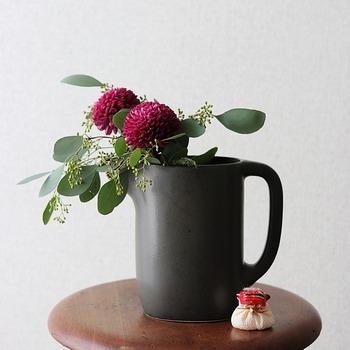 ぽってりとした質感のフラワーベースにちょこんとお花だけ顔を出したポンポンマム。お花だけだと、ちょっとお澄ましした印象ですが、ユーカリの葉が混じることでキュートさがアップしました。