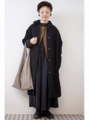 フレアがたっぷりと入ったAラインのワンピースは素材感を揃えた重ね着で重苦しくならないよう、調整しています。