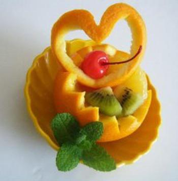 オレンジの上部分をハートにカットし、下部はジグザグに切り中をくり抜いて器に。他のフルーツも追加して彩りよく仕上げましょう。