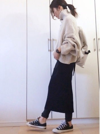 ボリューミィーなオフホワイトニットには、タイトな黒スカート+ほっそり黒レギンスがオススメ。髪もタイトにまとめて、手首や足首は出すなど、全体のボリューム感にメリハリをつけることが大事。