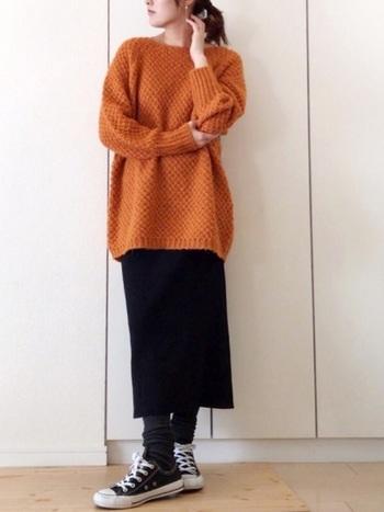 オレンジのざっくりニットに黒のロングスカートを合わせたレギンススタイル。黒コンバースに足元をくしゅっとできる14分丈のブラック系レギンスを合わせると、ほどよくカジュアルダウンでき、おしゃれ度もアップ!