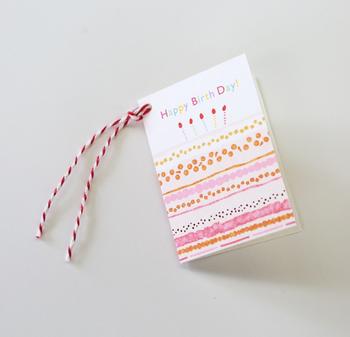 ケーキのモチーフが可愛らしいカードはミニサイズです。飾りに付けられた紅白の紐が、どこか和風でおめでたい雰囲気なのがかわいらしい。
